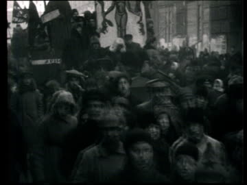 1922 montage b/w people taking part in 'agitprop' demonstration against church ruling, dressed up in costumes, holding banners with caricatures and walking with floats/ moscow, russia - tidigare sovjetunionen bildbanksvideor och videomaterial från bakom kulisserna