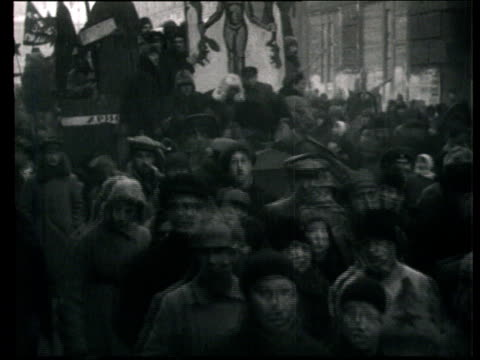 stockvideo's en b-roll-footage met 1922 montage b/w people taking part in 'agitprop' demonstration against church ruling, dressed up in costumes, holding banners with caricatures and walking with floats/ moscow, russia - 1920