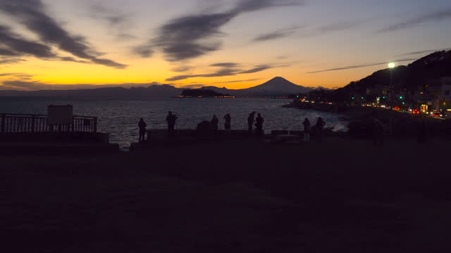 写真を撮る人。稲村ヶ崎から夕暮れ時の富士山と江ノ島 - 相模湾点の映像素材/bロール