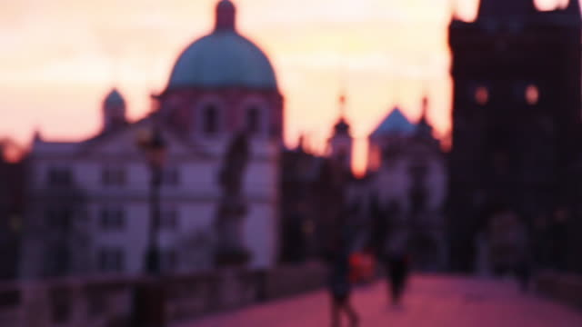 People taking pictures with smartphone during the beautiful sunrise over the Prague city from the Charles Bridge with the city landmarks on the background.