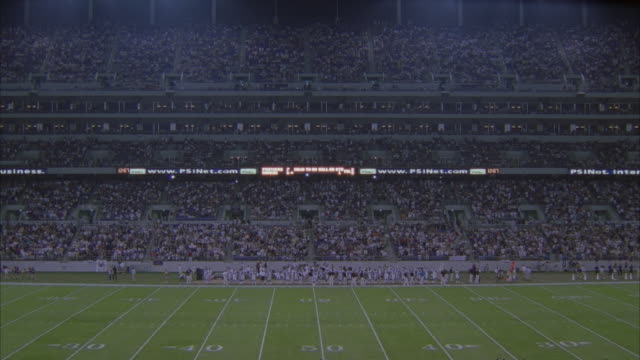LS people taking seats on football stadium, football team on field