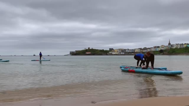 people taking stand up paddle board lesson arrive back to shore at tenby north beach on july 14, 2020 in tenby, wales. united kingdom. - oar stock videos & royalty-free footage