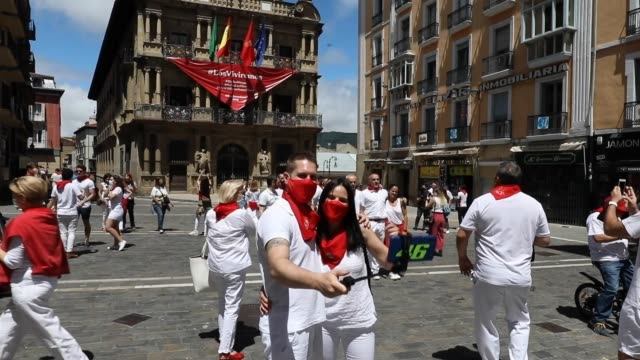 vídeos de stock e filmes b-roll de people talk a selfie photo in front of the ayuntamiento in consistorial square just past noon as the chupinazo commences the start of the cancelled... - meio dia