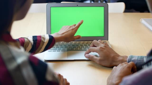 vídeos de stock e filmes b-roll de people talking and using laptop with green screen, chroma key - sobre os ombros vista traseira