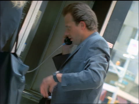 vidéos et rushes de canted pan people talking on outdoor pay phones / nyc - cinématographie