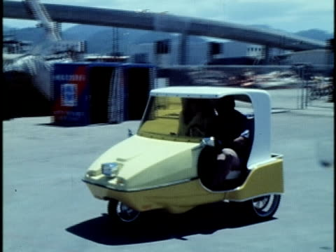 1975 montage people test driving a small three-wheeled electric car prototype in industrial area/ hawaii islands, usa/ audio - 試運転点の映像素材/bロール