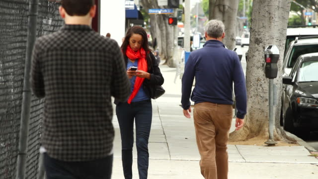 ms people texting on sidewalk / santa monica, california, united states - abblenden stock-videos und b-roll-filmmaterial