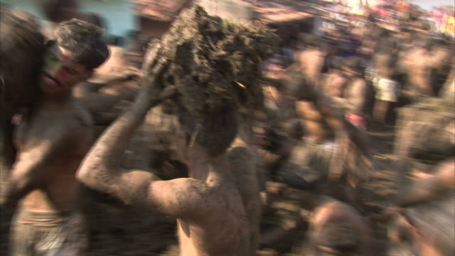vidéos et rushes de people throw cow dung at one another during the hindu gorehabba festival. - fête religieuse