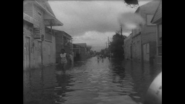 vídeos de stock e filmes b-roll de people tidying debris along the shoreline / cu rushing water / people moving down a flooded street / national guard directing traffic in high winds /... - dirigir