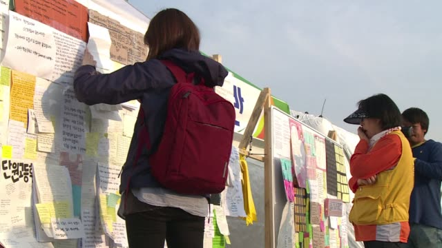 People tie ribbons and leave messages on a wall of condolence for the dead and missing of the South Korean ferry disaster