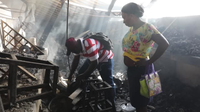 People to salvage her items as firefighters work to put out a blaze at PortauPrince's historic Iron Market on February 13 2018 in PortauPrince Haiti...