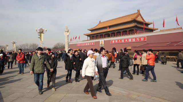 vídeos de stock, filmes e b-roll de people tourists walk past tiananmen gate in beijing people walk past a portrait of former chinese leader mao zedong at tiananmen gate in beijing... - portão da paz celestial de tiananmen