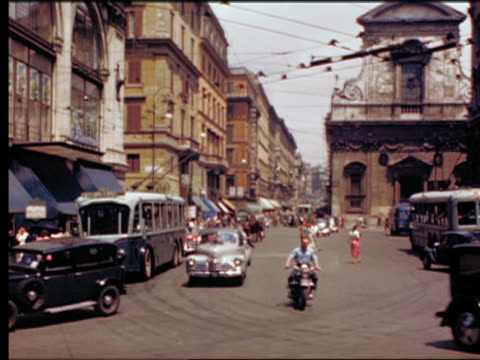1949 people + traffic with scooter, cable bus + wagon on busy city street / Rome, Italy