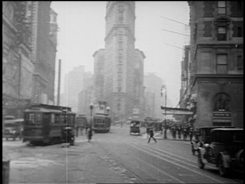 vídeos de stock, filmes e b-roll de b/w 1920 people + traffic with trolleys + cars on 5th avenue + broadway at flatiron bldg / nyc - 1920