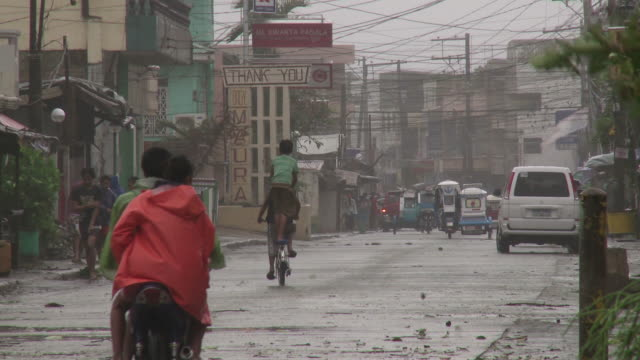 people travel along street as strong typhoon winds hit. super typhoon megi or juan, ne luzon, philippines oct 2010 / audio - record breaking stock videos & royalty-free footage