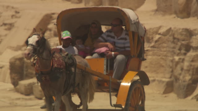 People travel in a cart next to the ancient pyramids of Giza, Egypt.