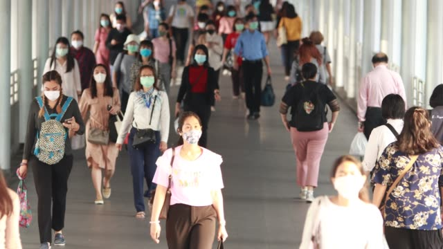 people traveling to work during the outbreak of corona virus or covid-19 to protect themselves by wearing a mask to prevent infection. - editorial stock videos & royalty-free footage