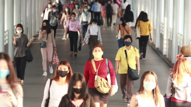 people traveling to work during the outbreak of corona virus or covid-19 to protect themselves by wearing a mask to prevent infection. - editorial stock-videos und b-roll-filmmaterial