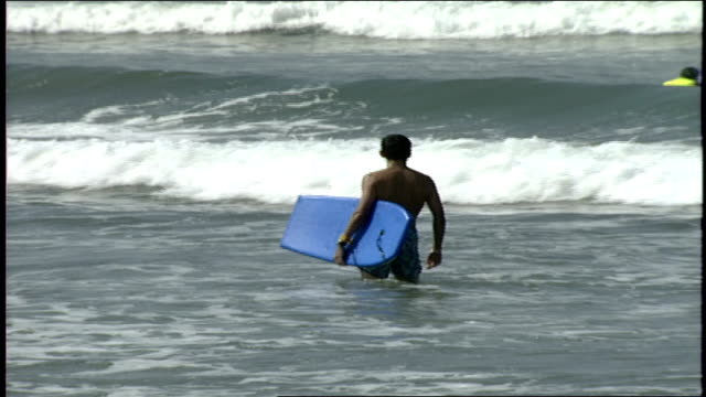 people trying to ride boogie board through waves in huntington ca - water sports equipment stock videos and b-roll footage