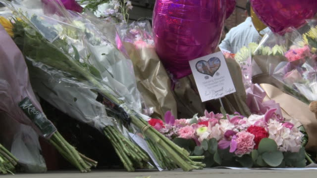 people turn out to light candles bring flowers balloons and cry at the memorial outside the manchester arena where 22 were killed and 59 injured when... - manchester england stock videos and b-roll footage