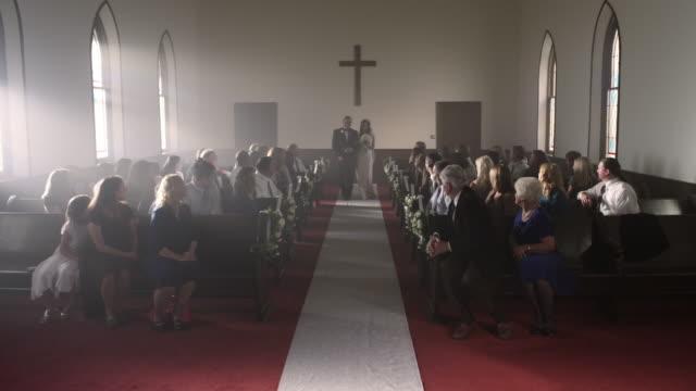 vidéos et rushes de people turning to watch a father escort a bride down the aisle. - église