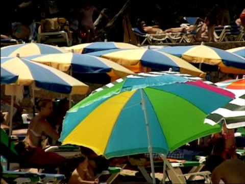 stockvideo's en b-roll-footage met ms, people under sun umbrellas relaxing on beach, ibiza, spain - zonnescherm gefabriceerd object