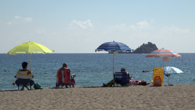 people under sunshades at sandy beach - sardinien stock-videos und b-roll-filmmaterial