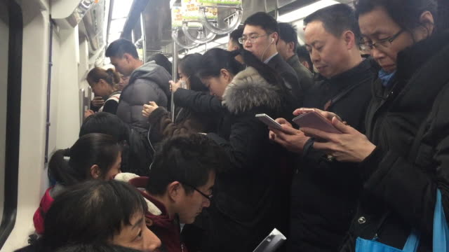 People use cellphones on the metro at rush hour on Feb 14 2017 in Beijing China