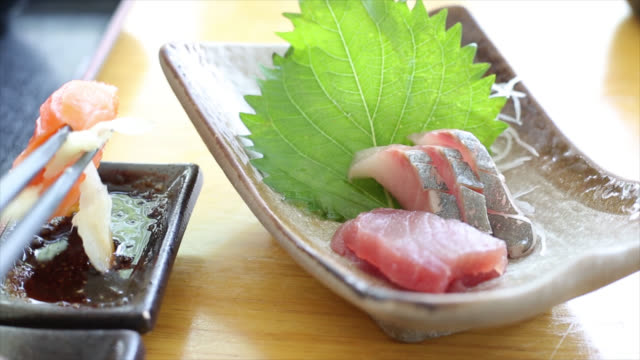 People use chopstick to hold sashimi
