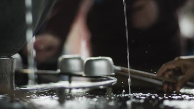 vídeos de stock, filmes e b-roll de people use dippers during ritual purification at senso-ji temple, asakusa. - templo asakusa kannon