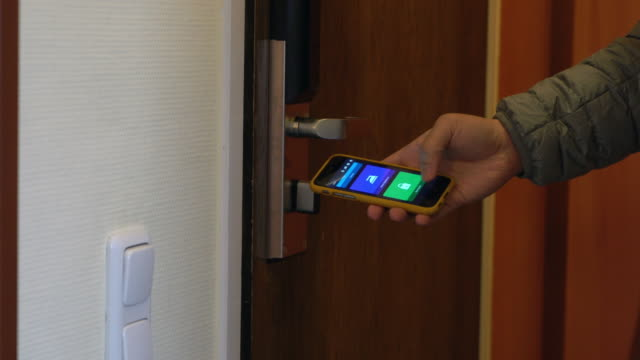 people use smartphone to control the door. smart home and home automation technology - smart stock videos & royalty-free footage