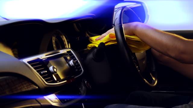 vídeos de stock, filmes e b-roll de as pessoas usam o pano de microfibra amarelo para limpar o console, o interior do carro é um couro preto bonito, azul luz clarão luz no cinema - secar