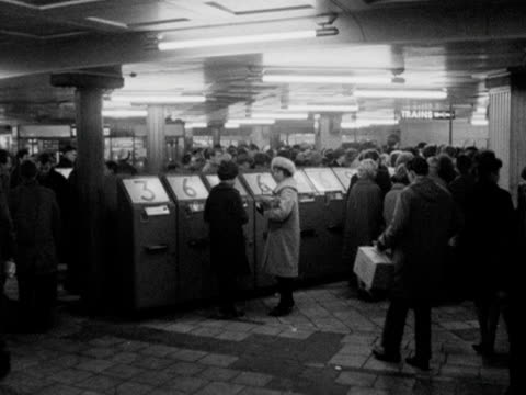 people use ticket machines in the busy ticket hall at piccadilly circus station; 1963. - ロンドン地下鉄点の映像素材/bロール