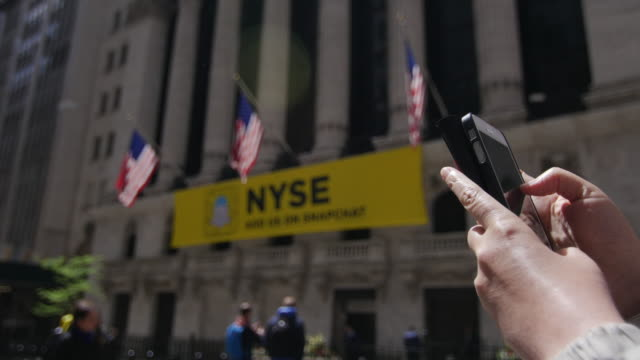 People using cellphone in front of NYSE building, New York Stock Exchange at Wall Street