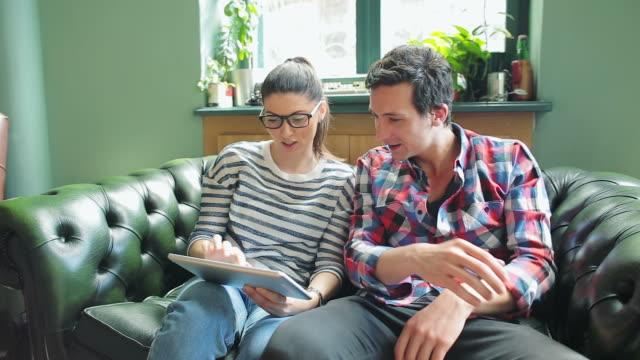 People using digital tablet in coffee shop.