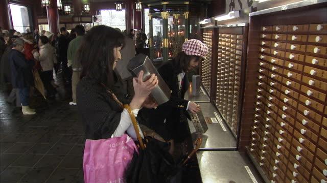 ms zi people using fortune sticks at senso ji, tokyo, japan - luck stock videos & royalty-free footage