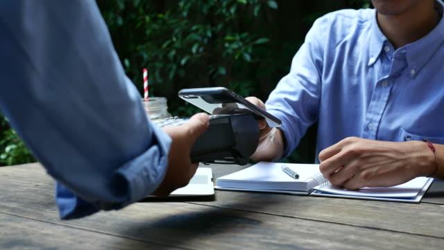 vídeos de stock, filmes e b-roll de povos que usam o telefone móvel que paga o pagamento sem contato no café - compra com cartão de crédito