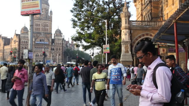 people using mobile phones on streets in mumbai india on saturday 15 feb 2020 - railway station stock videos & royalty-free footage