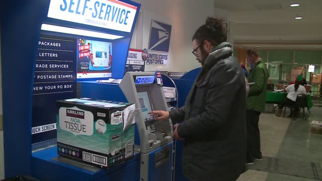 people using self-service machines at usps office during holiday season in chicago on dec. 21, 2016. - postamt stock-videos und b-roll-filmmaterial