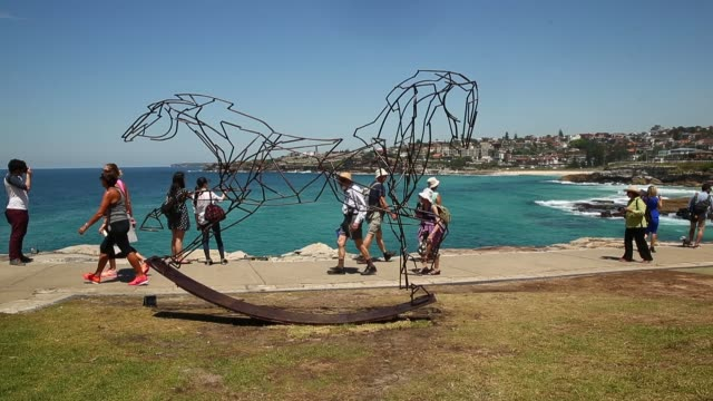 people view the various sculptures on display during the 2014 sculptures by the sea exhibition at marks park on october 23 2014 in sydney australia - sculpture stock videos & royalty-free footage