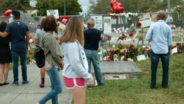 people visit a makeshift memorial setup in front of marjory stoneman douglas high school on february 19 2018 in parkland florida police arrested and... - trauernder stock-videos und b-roll-filmmaterial