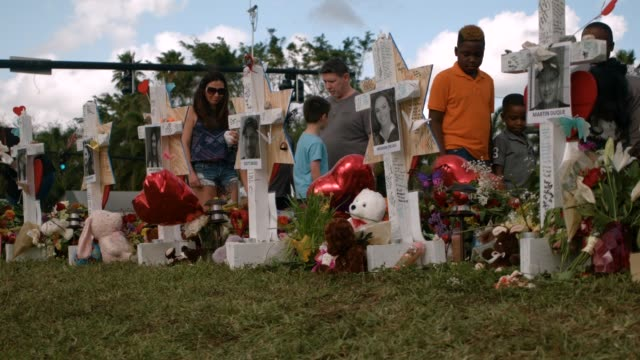 people visit a makeshift memorial setup in front of marjory stoneman douglas high school on february 19, 2018 in parkland, florida. police arrested... - minnesmärke bildbanksvideor och videomaterial från bakom kulisserna