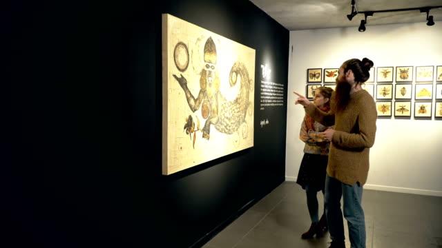 vídeos y material grabado en eventos de stock de personas visitan una exposición - museo de arte