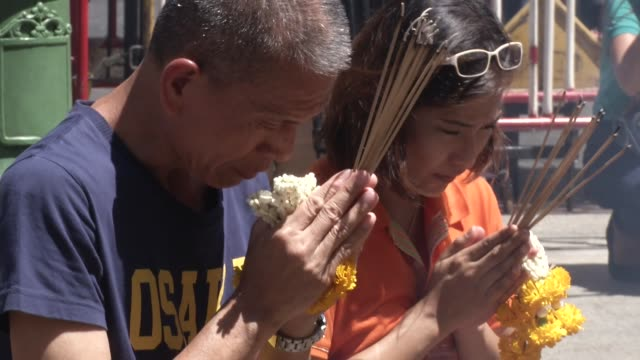 people visit erawan shrine after it reopened two days after a bomb exploded close to the shrine in the center of thailand's capital, bangkok, killing... - エラワン聖堂点の映像素材/bロール