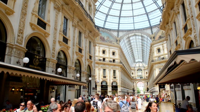 vídeos de stock e filmes b-roll de people visit galleria vittorio emanuele ii during a hot summer day the galleria vittorio emanuele ii is one of the world's oldest shopping malls it... - 1865