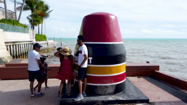 people visit the southernmost point buoy landmark next to the strait of florida during the seasonal king tides on october 26, 2019 in key west,... - buoy stock videos & royalty-free footage