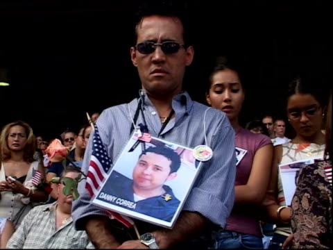 vs people w/ photos of dead loved ones hanging around their necks hispanic man in sunglasses solemnly holds american flag beneath large photo of... - missing persons stock videos & royalty-free footage