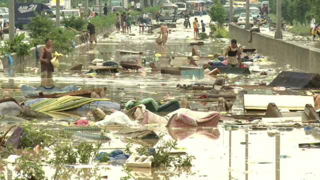 vidéos et rushes de people wade in filthy flood waters in manila - catastrophe naturelle