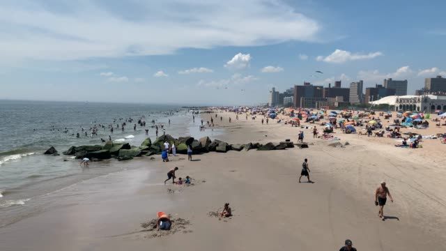 stockvideo's en b-roll-footage met people wade in the water at the beach at coney island on july 19, 2020 in the brooklyn borough of new york city. much of the east coast is... - zwembroek