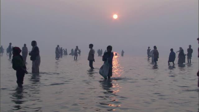 stockvideo's en b-roll-footage met ws tu people wading and praying in t waters of  ganges river / kanpur, uttar pradesh - bidden
